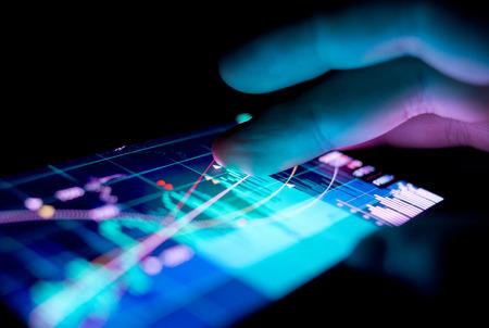 Un homme d'affaires vérifier les graphiques boursiers sur un appareil mobile. La technologie et le travail sur la route.