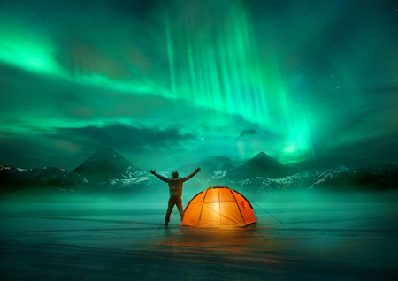 A man camping in wild northern mountains with an illuminated tent viewing a spectacular green northern lights aurora display. Photo composition. photo