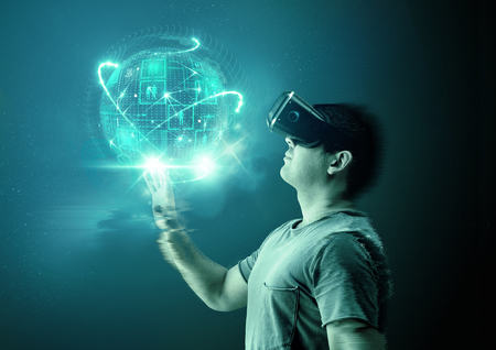 A young man wearing virtual reality (VR) goggles and headset with a projection of a digital world.