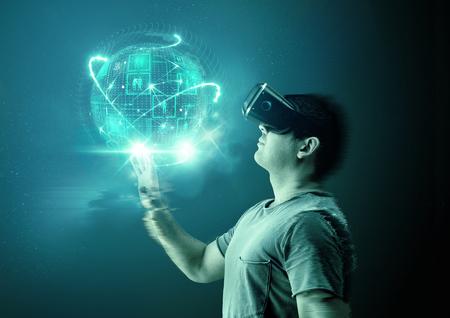 Un jeune homme utilisant des lunettes de visée virtuelle (VR) et un casque avec une projection d'un monde numérique. Banque d'images