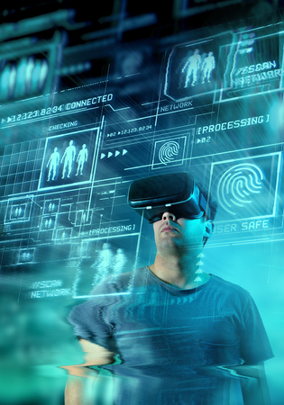 A young man wearing virtual reality (VR) goggles and headset with a projection of a digital information on display. Stock Photo