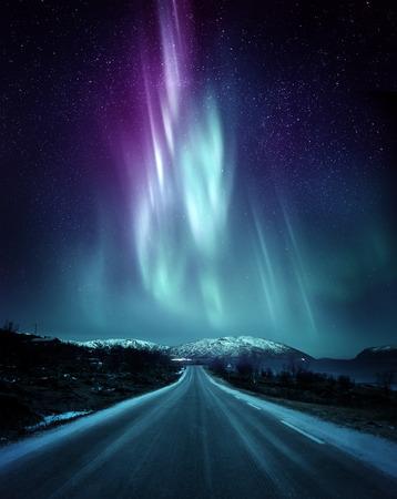 Eine ruhige Straße in Norwegen mit einer spektakulären Nordlicht-Aurora-Anzeige, die den Nachthimmel über den Bergen erhellt. Ein beliebtes Ziel innerhalb des Polarkreises für die Jagd nach Nordlichtern. Foto-Zusammensetzung. Standard-Bild