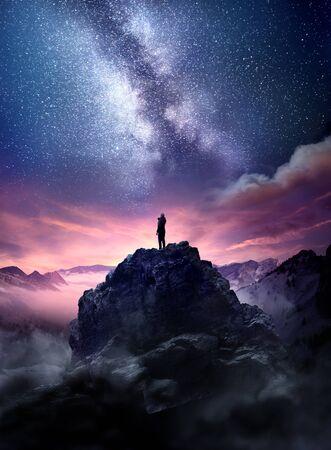 Nachthimmel-Langzeitbelichtungslandschaft. Ein Mann steht auf einem hohen Felsen und beobachtet, wie die Sterne in den Nachthimmel aufsteigen. Foto zusammengesetzt.