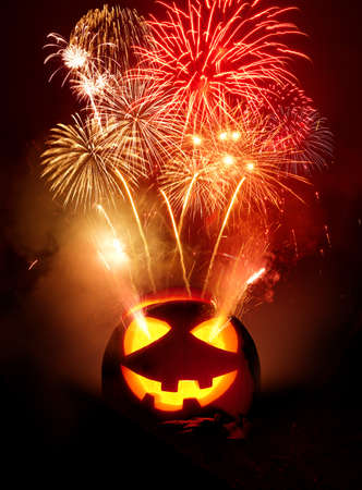 Halloween party background. A jack O lantern carved pumpkin glowing with fireworks being released into the night sky. photo composite. 写真素材