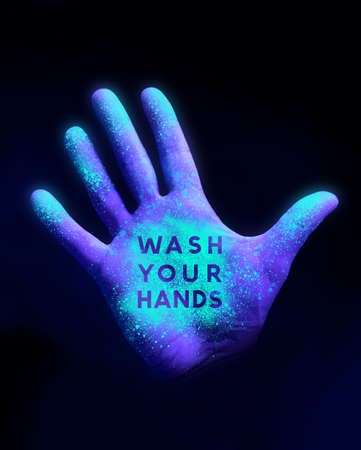 Stop the spread of desease. A human hand glowing from UV ultra violet light showing bacteria and viruses. wash your hands Concept. 写真素材