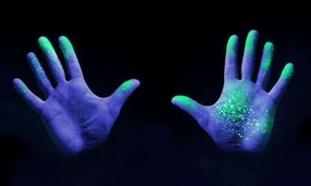 Human hands glowing from UV ultra violet light showing bacteria and viruses on a black background, showing the importance of hand washing.