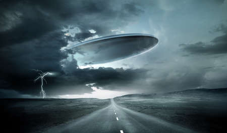 A large alien spaceship emerging from storm clouds on earth. 3D illustration. Zdjęcie Seryjne