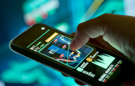 A businessman checking cryptocurrency and stock prices on a mobile app. Investing using a smartphone online.