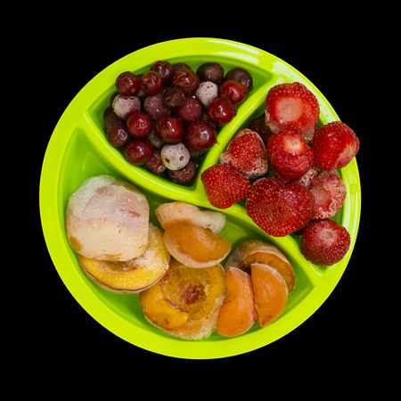 Frozen peaches apricot cherries strawberries isolated on black background photo food