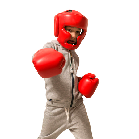 Sporty boy doing boxing exercises, making direct hit. Photo of young man isolated on white background. Strength and motivation