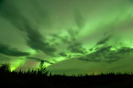 northern light: Bright fall aurora over Alaska-Canada Highway, with clouds moving beneath