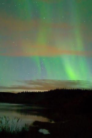Faint twilight aurora over the Yukon River, near Whitehorse, Yukon Territory, Canada. Thin clouds lit by faint city light. Shot near the Alaska-Canada (Alcan) Highway.