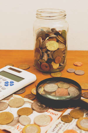 Statistics and research table on finance and business and money with calculator, magnifying glass, coins and banknotes