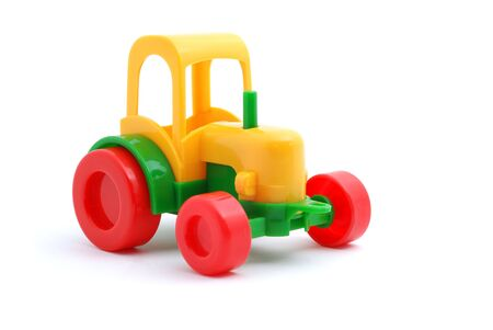 Small yellow toy tractor isloated on white photo