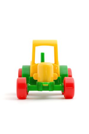 Small toy tractor a side view on white photo