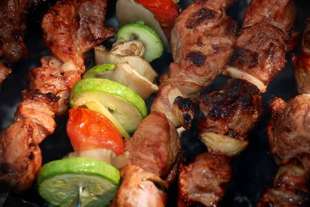 The shish kebab with vegetables prepares on fire photo