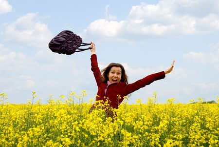 throw up: The having fun girl in the field of yellow flowers