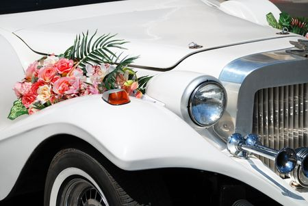 adorning: White wedding limousine decorated with flowers
