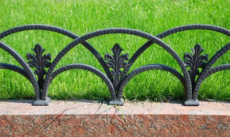 Decorative fencing near sidewalk in park and one yellow flower photo