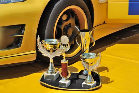 Trophies near a wheel of a yellow racing car Stock Photo - 5600706