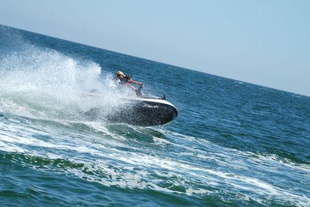 jet ski: Hombre en una de esqu� de alta velocidad de chorro con agua pulverizada Foto de archivo