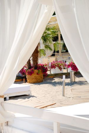 Area of a beach for comfortable rest with flowers and chaise longue photo