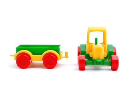 Small yellow toy tractor isolated on white photo