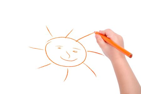 Childrens hand with pencil draws the sun, isolated photo