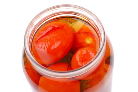 The clear glass jar of colorful pickled vegetables on white photo