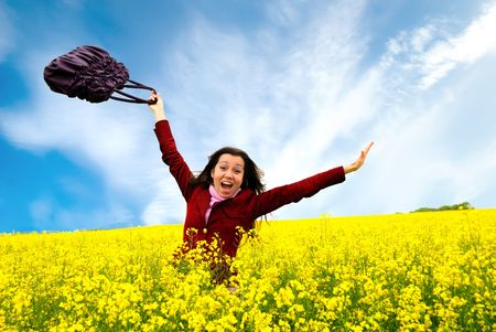 The having fun girl in the field of yellow flowers