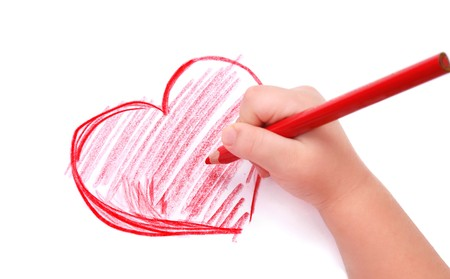 Childrens hand with pencil draws the heartl, isolated photo