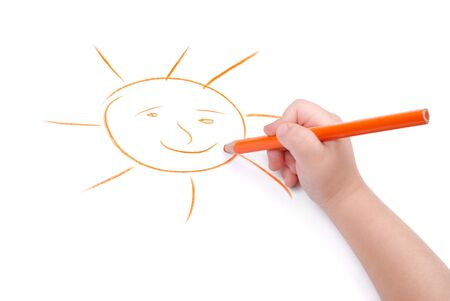 Childrens hand with pencil draws the sun, isolated
