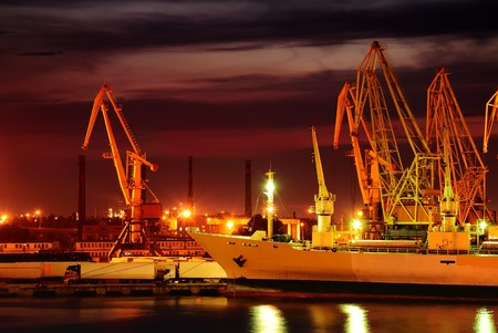 Port warehouse with cargoes and containers at night photo