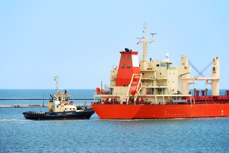 Tug boat helps to maneuver the ship in port photo