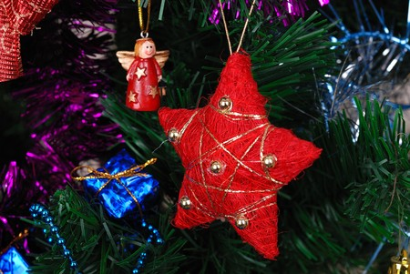 Red star hanging on fir tree with other decoration Stock Photo - 7983729