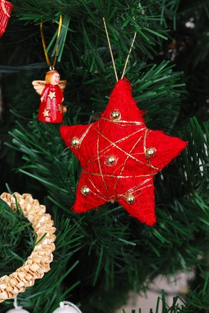 Red star hanging on fir tree with other decoration Stock Photo - 8063835