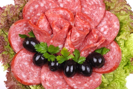 Tasty sausages on a plate with salad and olives photo
