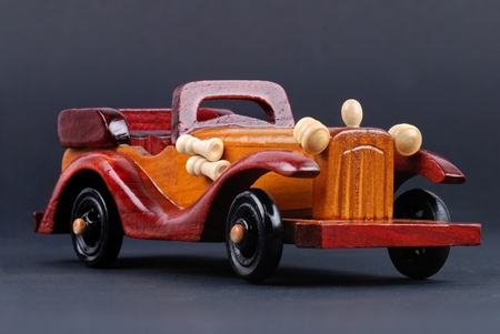 A toy car made of wood on black photo