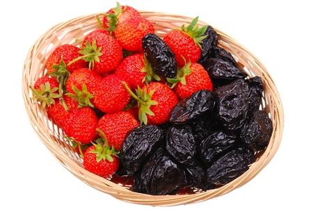 pruneau: Panier avec des fraises fra�ches et pruneaux isol� Banque d'images