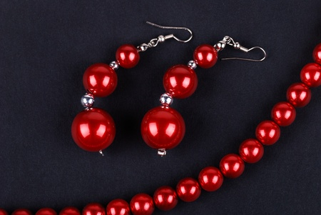 red beads and necklaces on dark photo