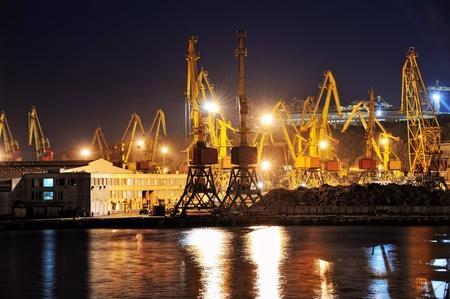Vista nocturna del puerto industrial con cargas