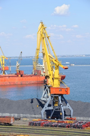 Industrial port with cargo. Coal, tubes, ship, cranes. Railroad and car. photo