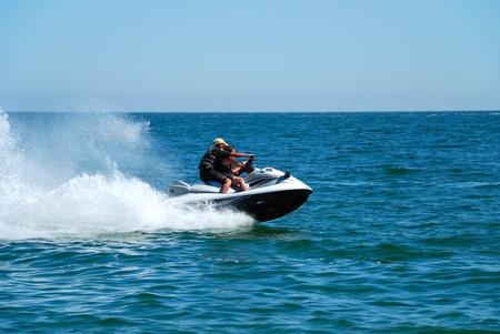 Człowiek na wysokim jet ski prędkości strumieniem wody