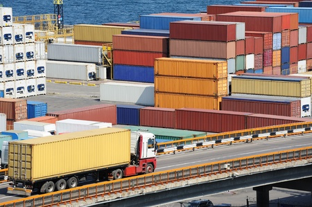 truck transports container to a warehouse near the sea photo