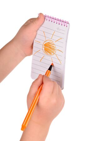 children's hands hold notebook with a painted sun. isolated photo