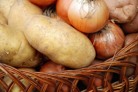 harvest of potatoes and onions in a basket as background photo