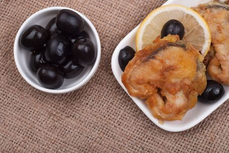 Fried fish with a lemon and olives on sackcloth photo