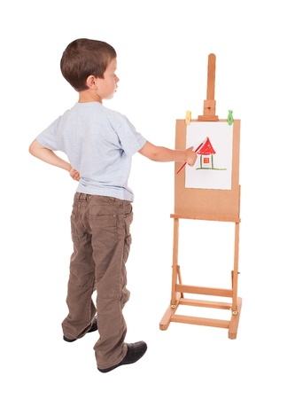 boy paints house on easel photo
