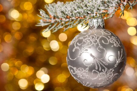 argent: christmas ball on fir tree branch and golden background