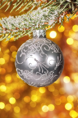 christmas ball on fir tree branch and golden background photo